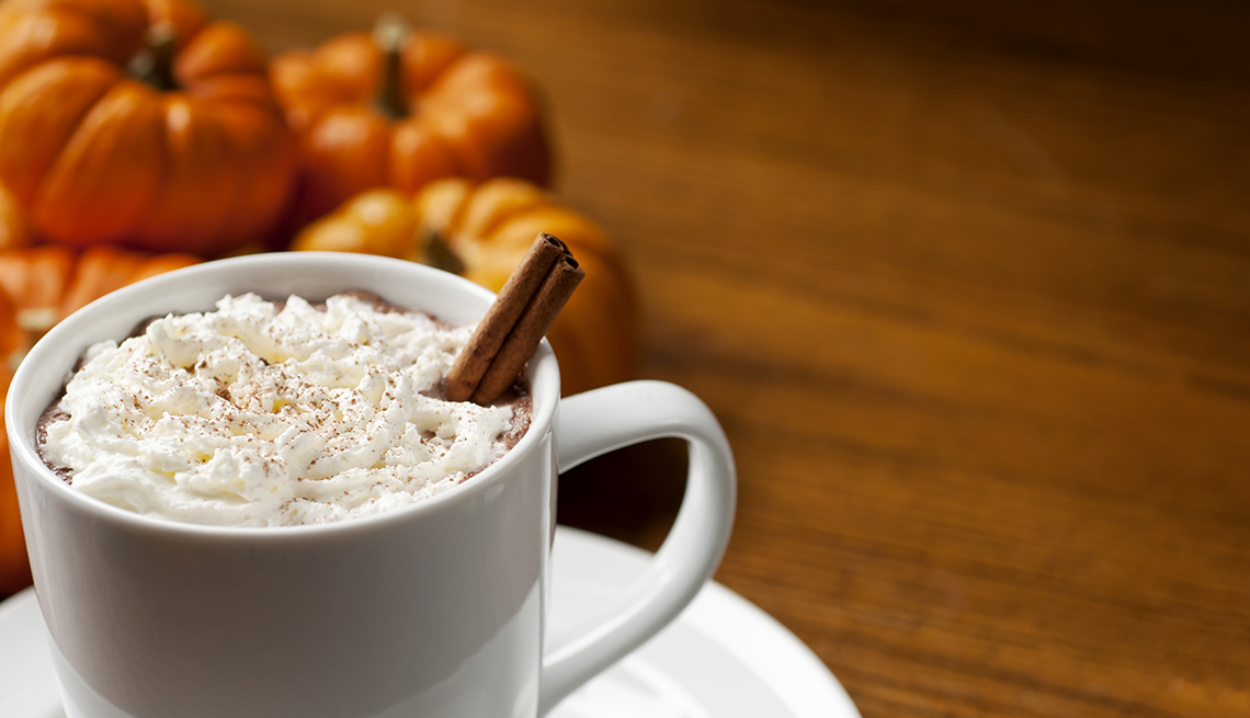 cup of pumpkin spice latte with whipped cream and cinnamon stick. Pumpkins in background.