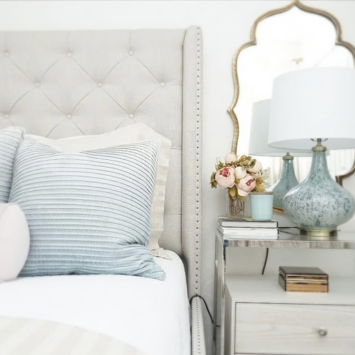 closeup of bedrooms design with light colors and mirror behind a lamp to make it appear larger
