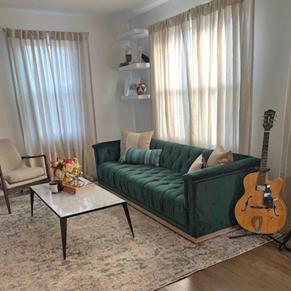 Una sala de estar con cortinas más claras, techos altos y muebles con patas de madera