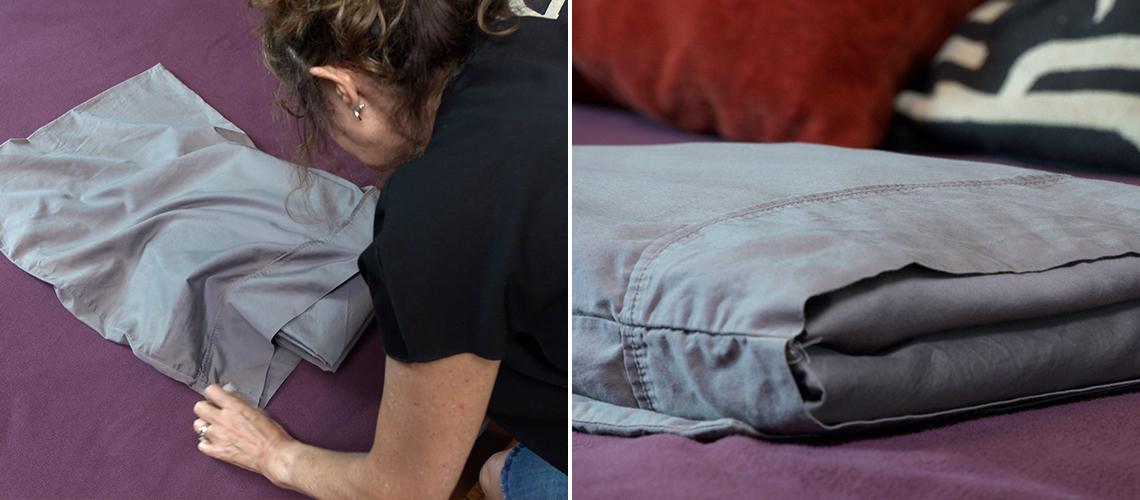 item 8 of Gallery image - Mujer desliza las sábanas dobladas dentro de una de las fundas de almohada