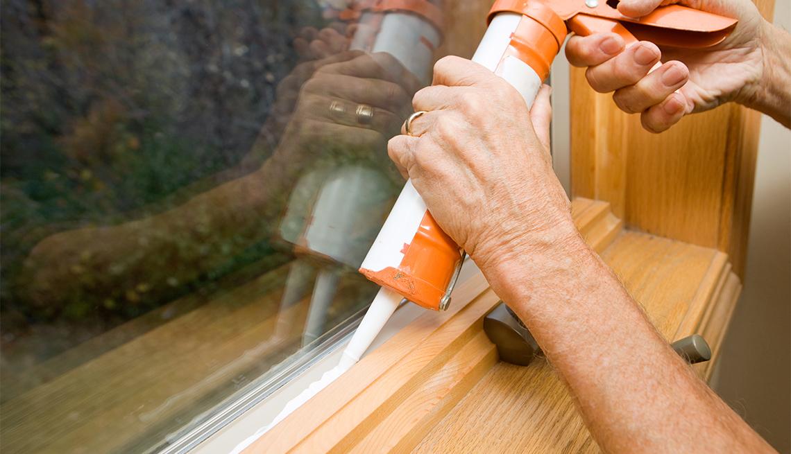 person caulking a window sill