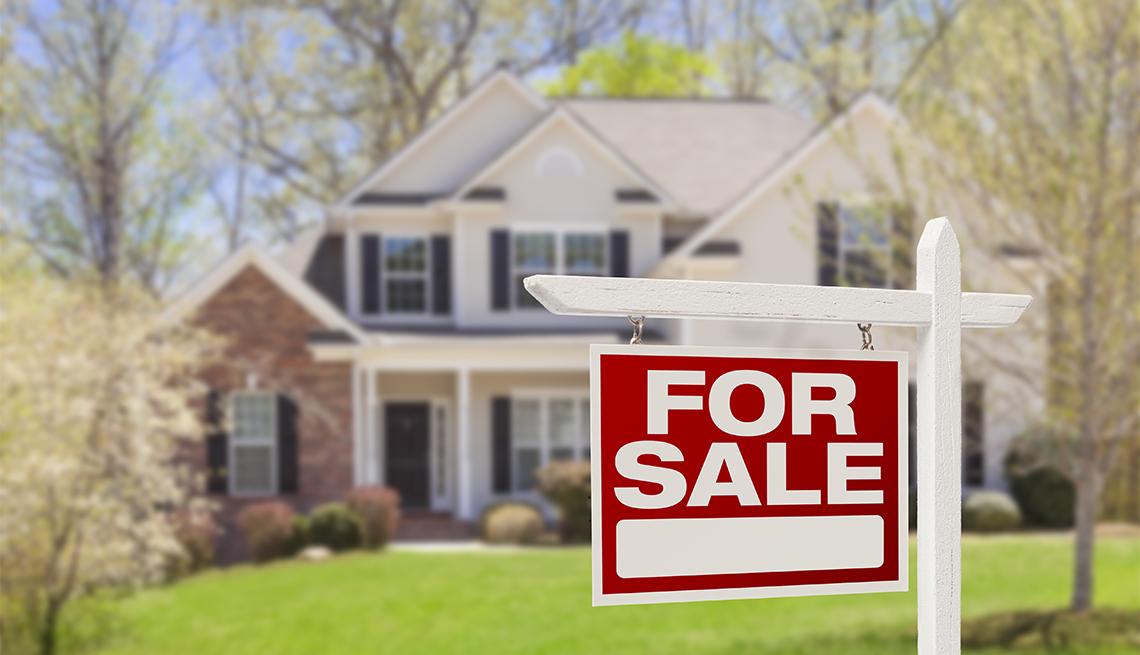 Casa con cartel de venta en el patio