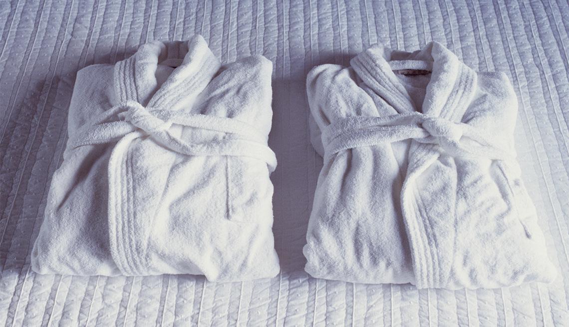 2 hotel bathrobes on a bed