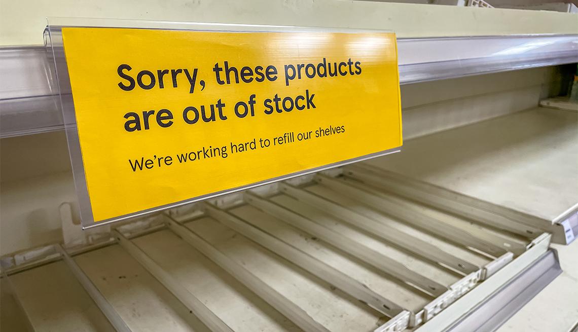 Estantes vacíos en una tienda y cartel amarillo que dice agotado