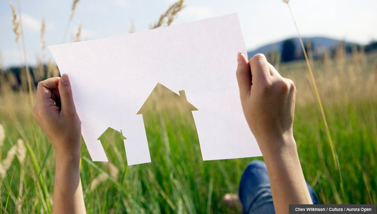A person holding up a paper cut-out of a house in front of a grassy field.