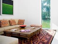 Decoración con un toque étnico - Sala interior con mesa de centro y sofa al fondo.
