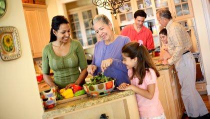 Abuelos, padres e hijos cocinando en casa