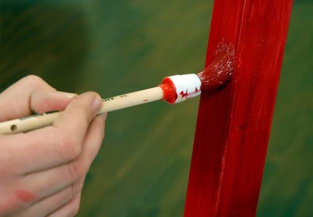 Hombre pintando una madera de rojo - 10 ideas para arreglar su casa