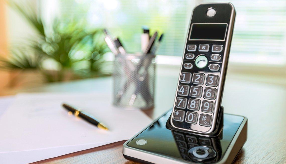 Teléfono sobre una mesa con papel y lapiceros