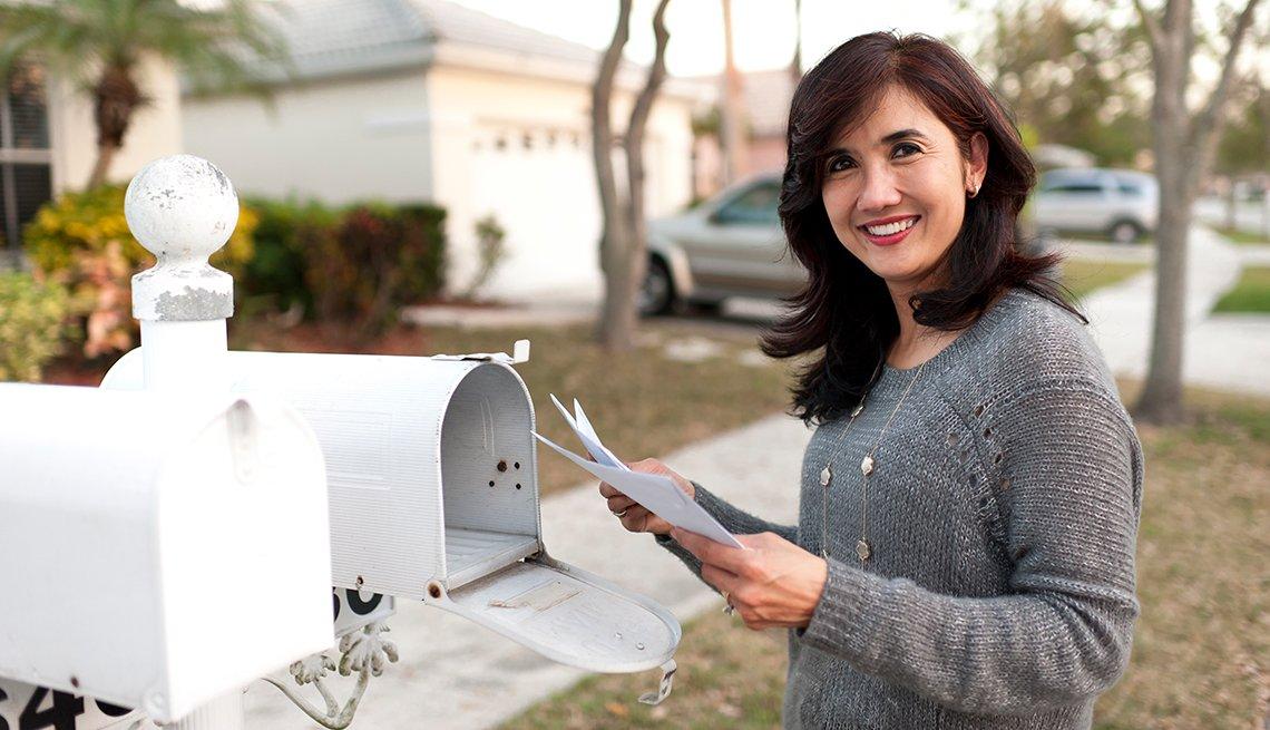 Mujer recogiendo correo de un buzón afuera de casa