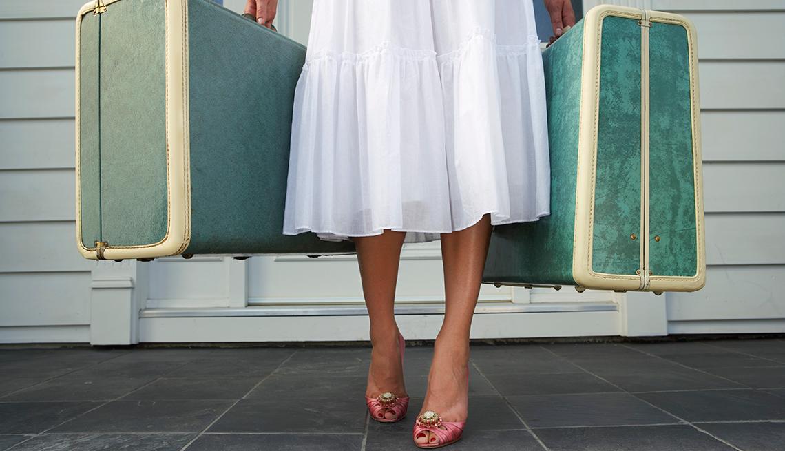 Mujer vestida de blanco saliendo de su casa con maletas antiguas