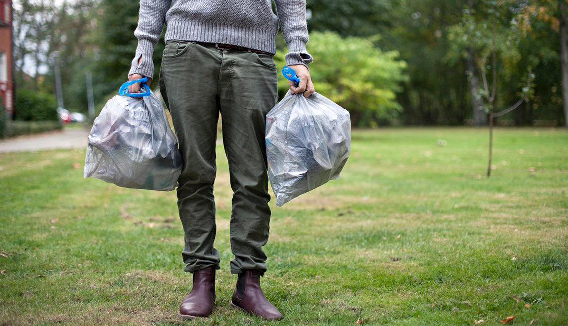 Medio cuerpo de un hombre en un jardín con bolsas de basura
