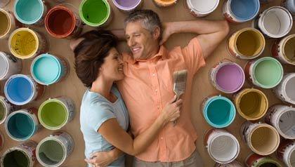 Pareja acostada al lado de muchos botes de pintura de todos los colores