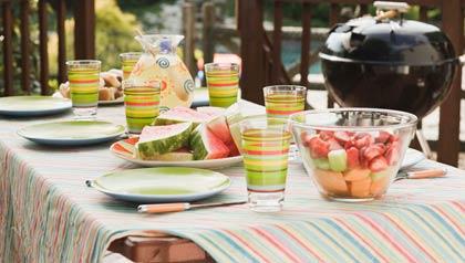 Una mesa al aire libre con una parrilla para cocinar - Fiestas para este verano