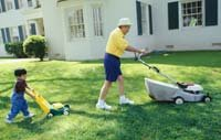 Grandfather and grandson (3-4) mowing lawn in garden, side view