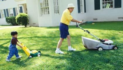 Abuelo y nieto cortando el césped en el jardín de su casa