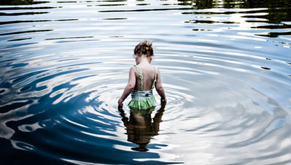 Lakes and mountains are a summer treat for grandchildren in Burlington-Vermont- a young girl plays in a lake