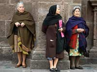 Aging in Mexico – Three elderly women wait while standing on a sidewalk
