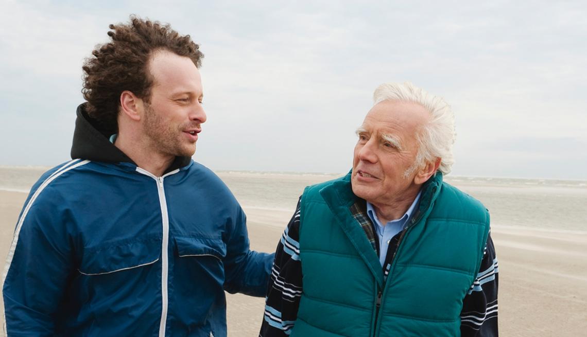 Padre e hijo caminando en la playa