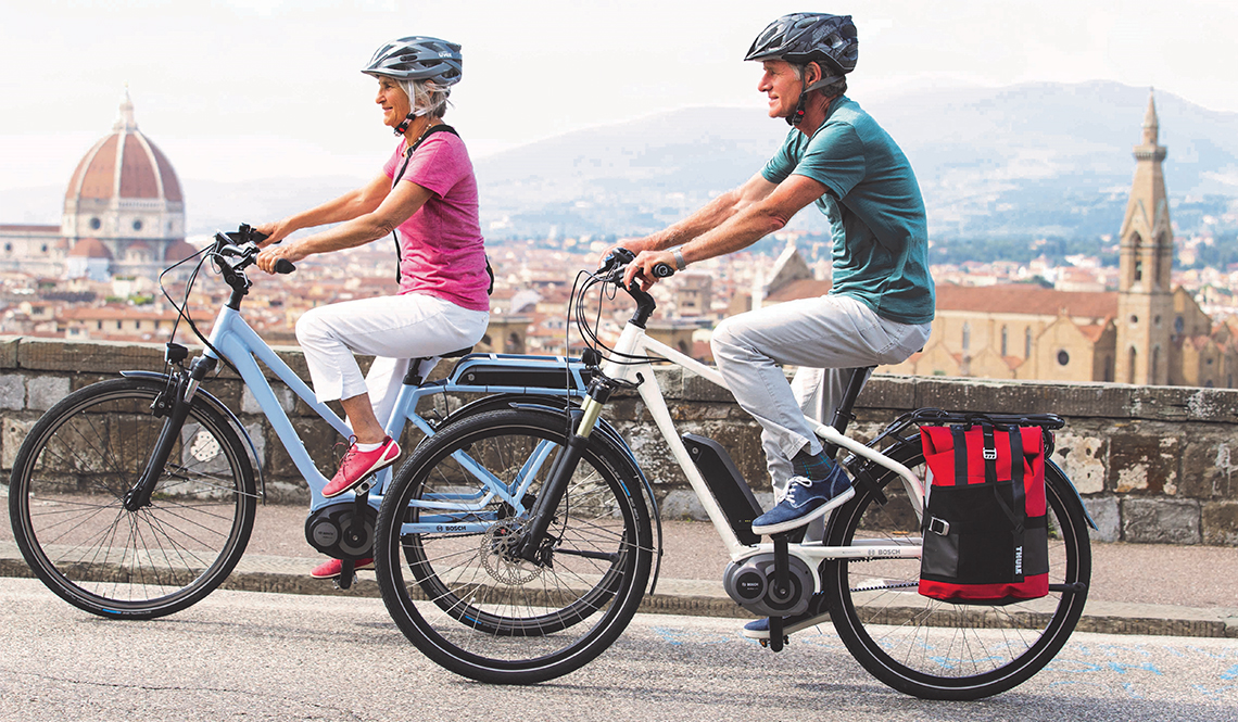 An older couple riding his and her Bosch-brand e-bikes.