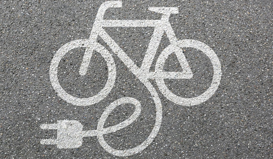 The image of a bicycle with an electric plug as seen stenciled on pavement with white paint.