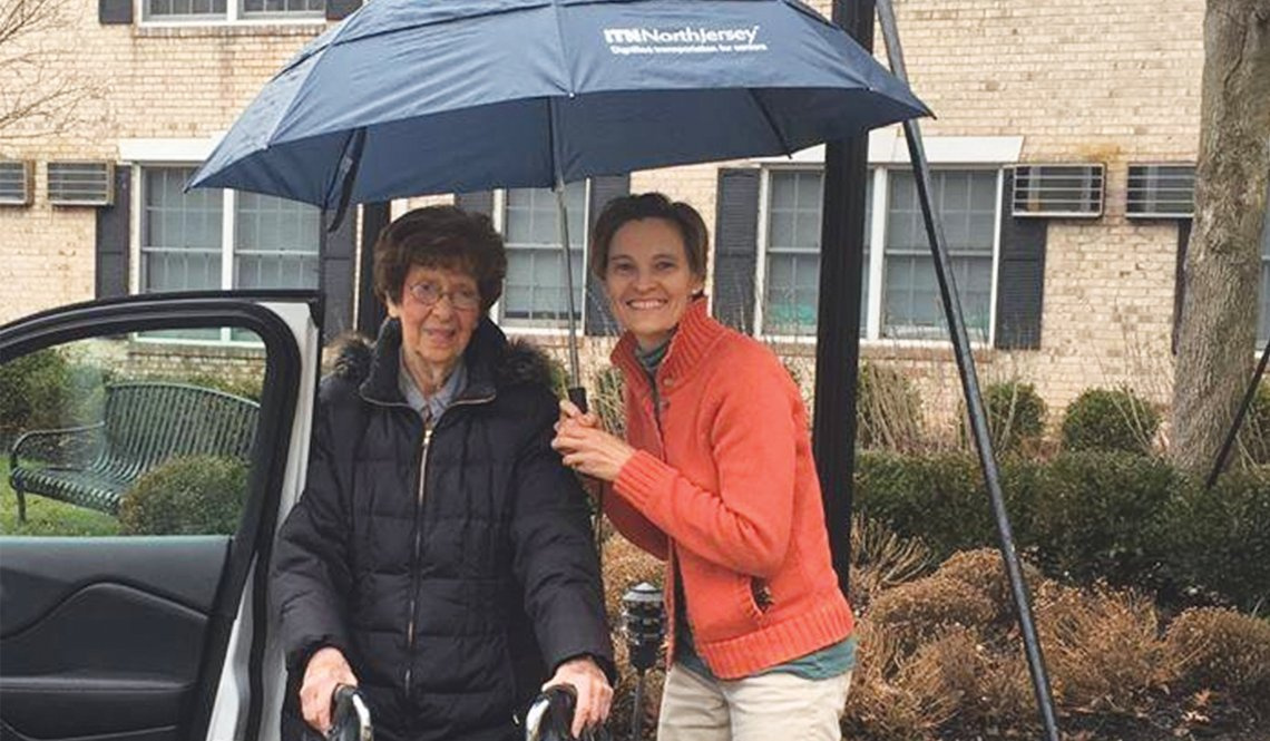 A volunteer driver from ITN Northern Jersey helps her client get to the car.