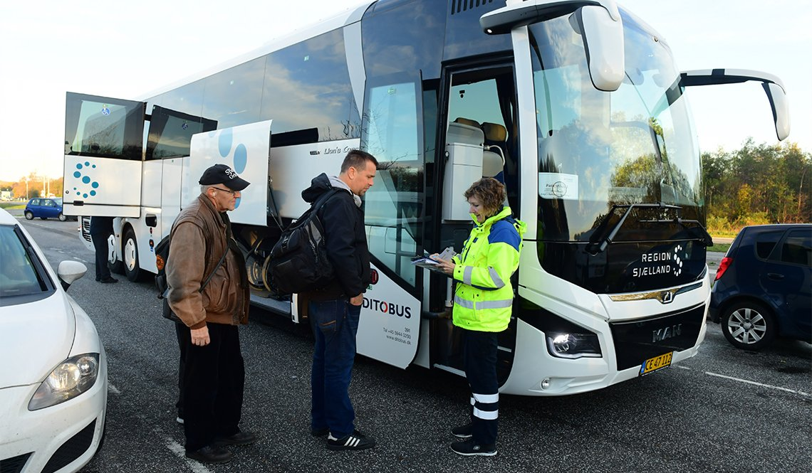 FlexTrafik passengers are checked in before boarding a hospital-bound bus