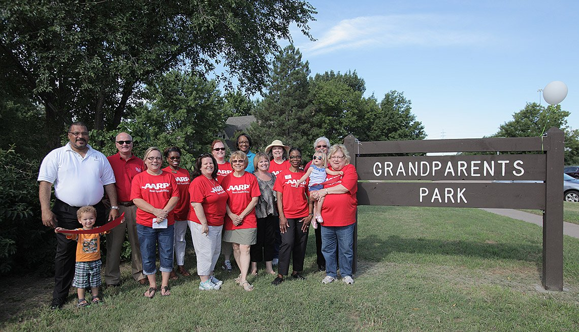 Families Pose In Front of Sign For Grandparents Park, Livable Communities, How To Build A Grandparents Park