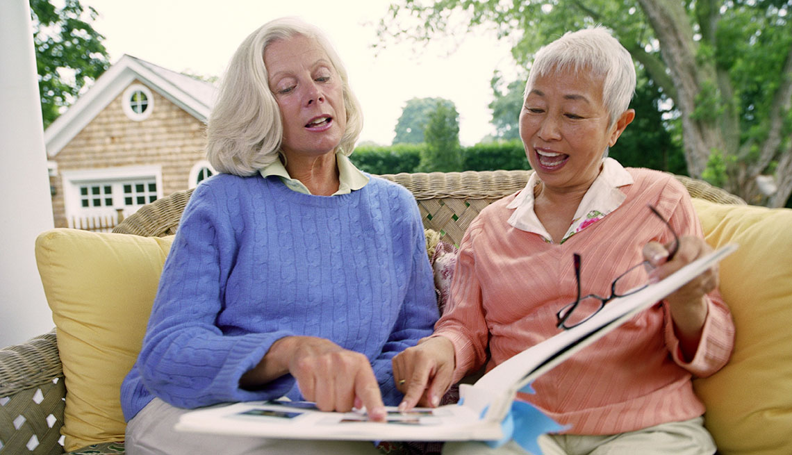 Two Mature Ladies Sitting On Porch And Looking At Photo Album, Livable Communities
