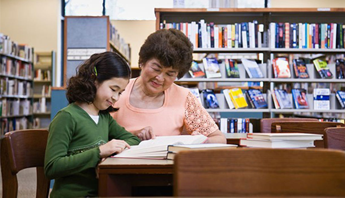 An older woman helps a young girl with homework.