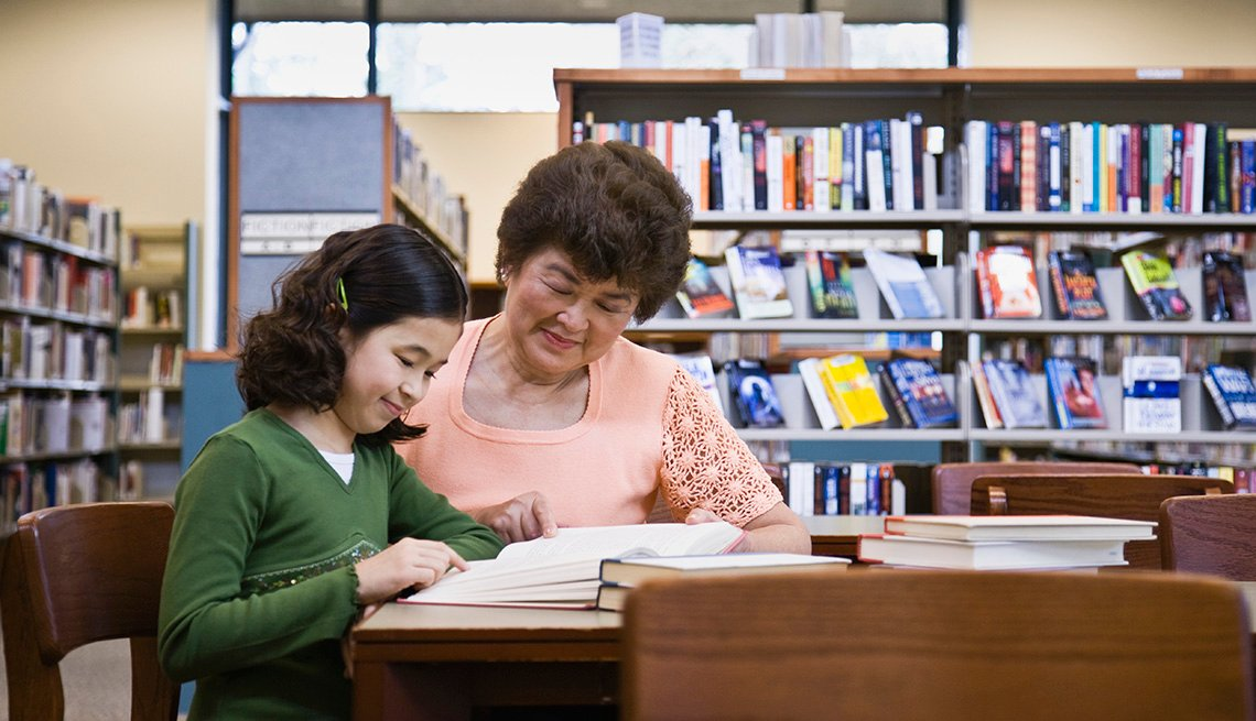 Social Inclusion And Respect, Mature Adult Woman Helping Young Girl Read In Library, Livable Communities, 8 Features Of An Age Friendly Community