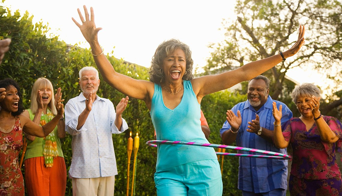 Mature African American Woman Laughs While Doing The Hula Hoop With Others Cheering Her On In The Background, Livable Communities, 8 Features Of An Age Friendly Community