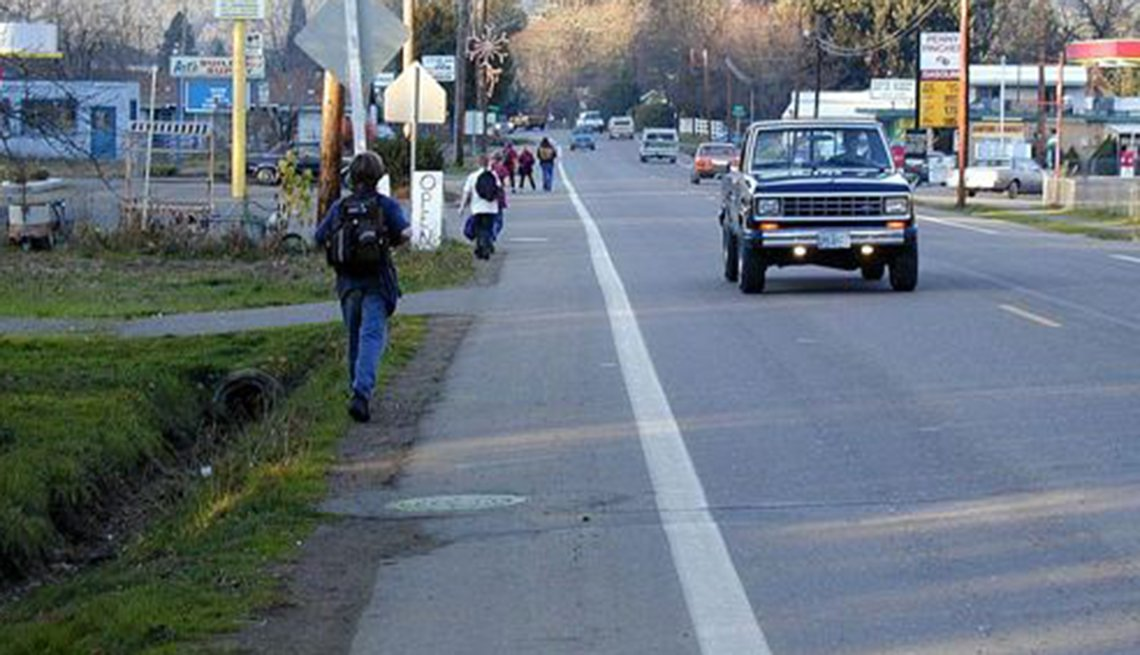 Students walk along a road with no sidewalks.