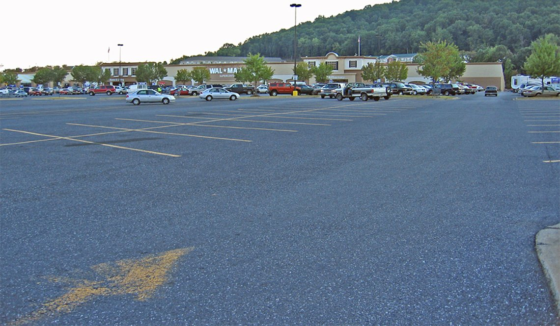 A vast, largely empty Wal-Mart parking lot.
