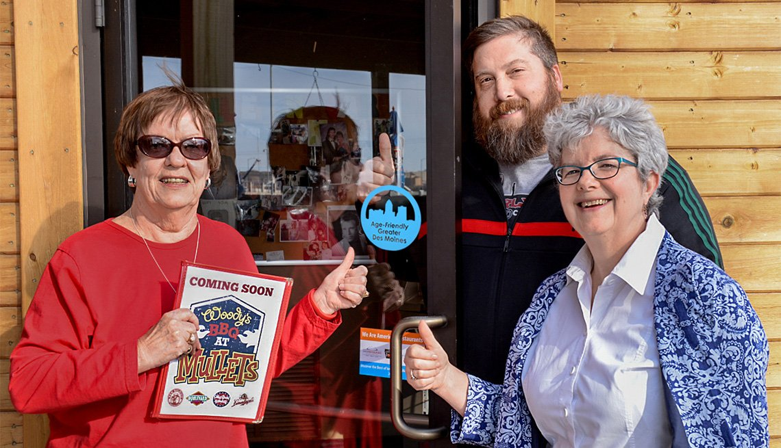 Two women and a man give a thumbs up to Mullets Restaurant in Des Moines being an Age-Friendly Business