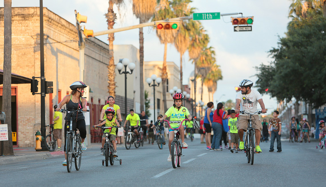 Family Rides Their Bikes on Main Street, Road, Buildings, Traffic Light, How To Create A Ciclovia Or Open Street Event