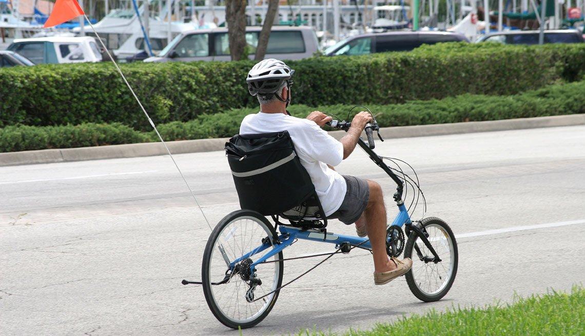 Hombre pedalea en un triciclo reclinable