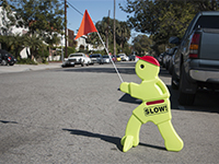 """A plastic """"slow traffic"""" man holds up a red flag on a wide street."""