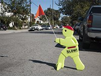 "A plastic ""slow traffic"" man holds up a red flag on a wide street."