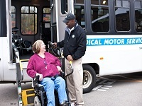 Bus driver helping woman in wheel chair out of the bus