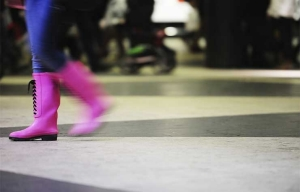 Woman walking in pink rain boots.