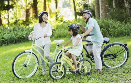 Little girl riding bicycles with grandparents