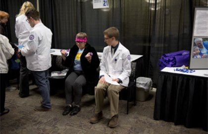 An older woman sits with a medical student at the Des Moines University senior health fair.