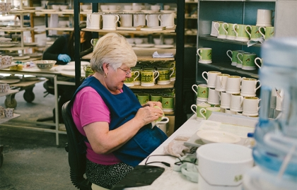 An older woman working at a pottery company in Stoke-on-Trent, United Kingdom