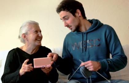 An older woman plays with a handheld computer game while a young man knits