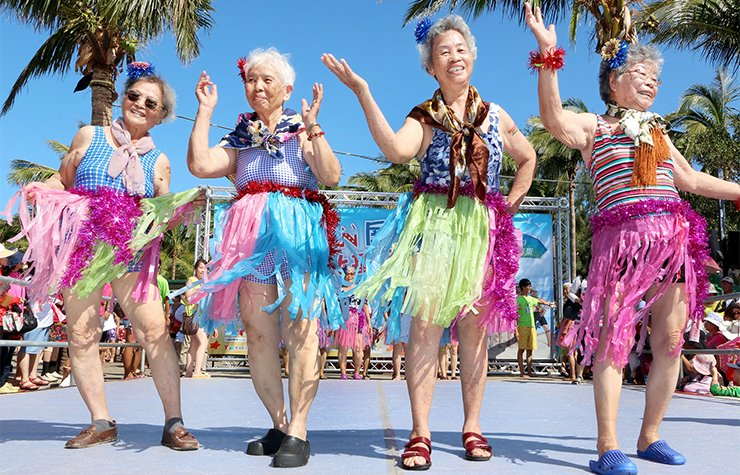 Older women in Taiwan perform on stage while wearing hula skirts