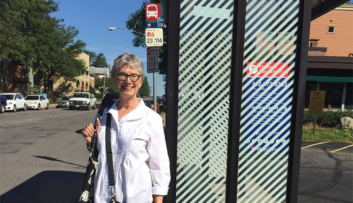 An Older Woman Smiles And Poses In Front Of A Bus Stop, Livable Communities, Why Older Adults Should Go Car-Free