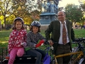 A father and his young twin daughters ride a bicycle built for three.