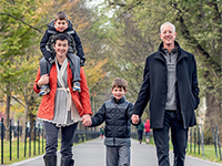 A man and woman go for a walk with their two young sons.
