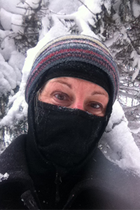 A bicyclist covers all but her eyes when cycling in the winter.
